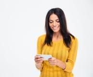 Mujer bonita sonriente que usa smartphone Foto de archivo
