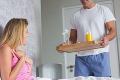 Mujer bonita sorprendida por el socio que trae el desayuno en cama Foto de archivo