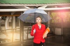 Mujer bonita tailandesa en el traje rojo de la oficina que sostiene el paraguas Foto de archivo