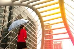 Mujer bonita tailandesa en el traje rojo de la oficina que sostiene el paraguas Fotos de archivo libres de regalías