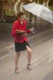 Mujer bonita tailandesa en el traje rojo de la oficina que sostiene el paraguas Foto de archivo libre de regalías