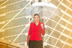 Mujer bonita tailandesa en el traje rojo de la oficina que sostiene el paraguas Fotografía de archivo libre de regalías