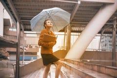 Mujer bonita tailandesa en el traje rojo de la oficina que sostiene el paraguas Imágenes de archivo libres de regalías