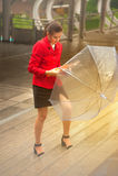 Mujer bonita tailandesa en el traje rojo de la oficina que sostiene el paraguas Fotos de archivo