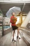 Mujer bonita tailandesa en el traje rojo de la oficina que sostiene el paraguas Fotografía de archivo