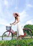 Mujer bonita y joven con la bicicleta Imagen de archivo libre de regalías