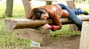Mujer borracha que duerme él apagado en un banco de madera Foto de archivo libre de regalías