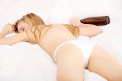Mujer borracha que duerme en cama Imagen de archivo