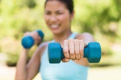 Mujer borrosa que ejercita con pesas de gimnasia en parque Foto de archivo libre de regalías