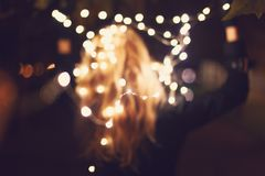 Mujer borrosa que juega con las luces de hadas en el invierno al aire libre imagen de archivo libre de regalías