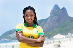 Mujer brasileña de risa en un jersey de fútbol en la playa Imagenes de archivo