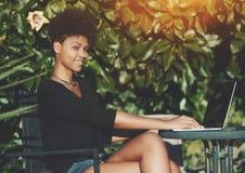 Mujer brasileña en parque público con el red-libro Imagenes de archivo