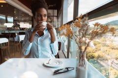 Mujer brasileña joven en café cerca de la ventana Imagenes de archivo