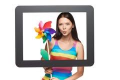 Mujer brillante con el molinillo de viento colorido Imágenes de archivo libres de regalías