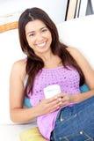 Mujer brillante que sonríe y que sostiene una taza de café Imagen de archivo