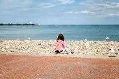 Mujer británica joven que se sienta en la 'promenade' de Llandudno que mira hacia fuera t Imagen de archivo libre de regalías