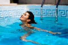 Mujer bronceada hermosa en el bikini que se relaja en piscina fotografía de archivo libre de regalías