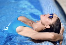 Mujer bronceada hermosa en el traje de baño azul que se relaja en balneario de la piscina cerca del chalet costoso en día de vera Fotografía de archivo libre de regalías