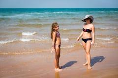 Mujer bronceada y muchacha que se colocan en la playa Imagen de archivo libre de regalías