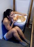 Mujer bulímica que siente la sentada culpable enferma en el piso del retrete que se inclina en el WC que come la pizza Foto de archivo