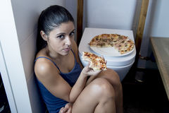 Mujer bulímica que siente la sentada culpable enferma en el piso del retrete que se inclina en el WC que come la pizza Fotos de archivo libres de regalías