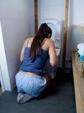Mujer bulímica que siente los fingeres culpables enfermos en la boca que vomita y que lanza para arriba en retrete del WC Fotografía de archivo