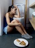 Mujer bulímica triste y deprimida joven que siente culpable enfermo después de vomitar la pizza en retrete del WC Imágenes de archivo libres de regalías