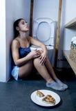 Mujer bulímica triste y deprimida joven que siente culpable enfermo después de vomitar la pizza en retrete del WC Foto de archivo libre de regalías
