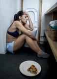 Mujer bulímica triste y deprimida joven que siente culpable enfermo después de vomitar la pizza en retrete del WC Fotografía de archivo
