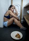 Mujer bulímica triste y deprimida joven que siente culpable enfermo después de vomitar la pizza en retrete del WC Foto de archivo