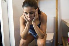 Mujer bulímica triste y deprimida joven que siente la sentada enferma en el WC del retrete que parece desesperado y enfermo Fotografía de archivo