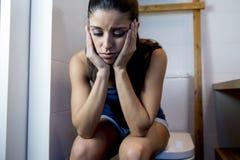 Mujer bulímica triste y deprimida joven que siente la sentada enferma en el WC del retrete que parece desesperado y enfermo Fotos de archivo libres de regalías