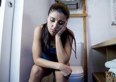 Mujer bulímica triste y deprimida joven que siente la sentada enferma en el WC del retrete que parece desesperado y enfermo Fotos de archivo