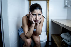 Mujer bulímica triste y deprimida joven que siente la sentada enferma en el WC del retrete que parece desesperado y enfermo Foto de archivo