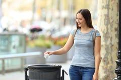 Mujer cívica que lanza un papel en un cubo de la basura Imagen de archivo libre de regalías
