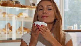 Mujer cabelluda del jengibre feliz que sonríe alegre, café delicioso de consumición almacen de metraje de vídeo