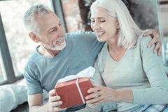 Mujer cabelluda gris satisfecha que toma el presente y que disfruta Fotos de archivo