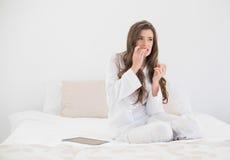 Mujer cabelluda marrón casual preocupante en los pijamas blancos que se sientan en su cama imagenes de archivo