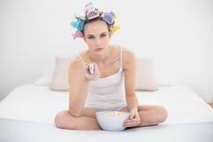 Mujer cabelluda marrón natural aburrida en bigudíes de pelo que ve la TV mientras que come las palomitas Fotos de archivo