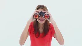 Mujer cabelluda morena que mira a través de los prismáticos almacen de video