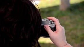 Mujer cabelluda negra que fotografía con una cámara vieja almacen de metraje de vídeo