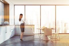 Mujer cabelluda oscura en la cocina blanca fotografía de archivo libre de regalías