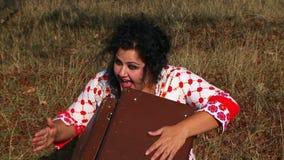 Mujer cabelluda oscura loca con la maleta en almacen de metraje de vídeo