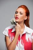 Mujer caliente joven con los dólares en fondo gris Imagen de archivo libre de regalías
