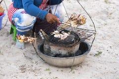 Mujer camboyana que vende los mariscos asados a la parrilla en la playa blanca Trabajo mal pagado de la gente local en Asia del S Fotografía de archivo