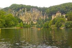 Mujer canoeing por el río delante de una montaña de la roca Imagenes de archivo