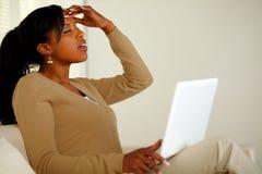 Mujer cansada con dolor de cabeza que hojea el Internet Imagen de archivo libre de regalías