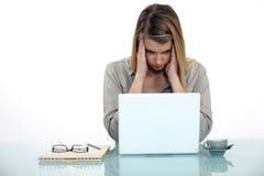 Mujer cansada del trabajo en su computadora portátil Imagenes de archivo