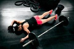 Mujer cansada después del entrenamiento duro que miente cerca de pesos Imagen de archivo