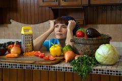 Mujer cansada en cocina entre verduras Imagen de archivo
